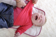 Crying baby being undressed Royalty Free Stock Image