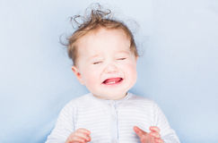 Crying baby on a blue blanket Stock Image