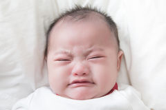 Crying baby boy. Asian baby boy crying on white bed Royalty Free Stock Photos
