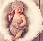 Crying baby boy in a basket Stock Images