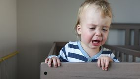 Crying baby boy in crib at home. Kid in the vest is sobbing stock footage