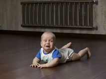 Crying baby. Boy on the dark wooden floor, indoor Royalty Free Stock Images