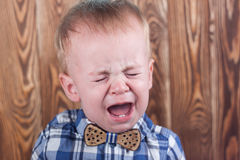 Crying baby boy. In a plaid shirt with a bow tie Royalty Free Stock Image