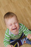 Crying baby boy. Portrait of a crying baby boy sitting on the floor Stock Photography