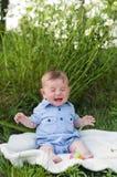 Crying baby boy sitting on blanket Royalty Free Stock Image