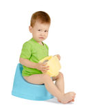 Crying baby boy sitting on a potty. Crying baby boy with toilet paper sitting on a blue potty isolated on white background Stock Images