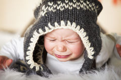 Crying baby boy with woolen cap. Stock Photos