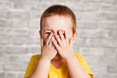Crying baby boy in a yellow T shirt covers his face with hands and shouts, studio on brick wall background stock image