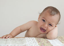 Crying baby child. Crying baby or toddler child, boy or girl, at home leaning on bed Royalty Free Stock Photography