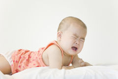 A crying baby. A Cninese baby is crying in bed Royalty Free Stock Photography