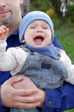 Crying baby on fathers hands outdoors Stock Photos