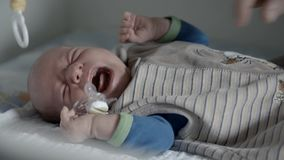 Crying baby getting pacifier. Close up of a woman's hands giving her baby a pacifier stock footage