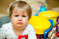Crying baby girl. Portrait of crying baby girl with toys in background Stock Photography