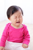 Crying baby girl. Portrait of crying baby girl on living room at home, asian child Royalty Free Stock Image