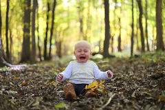 Crying Baby Girl in Autumn Woods under Yellow Maple Trees Royalty Free Stock Image
