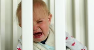 Crying baby in crib at home. Crying baby girl in crib at home close up stock video footage