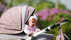 Crying baby-girl sitting in the baby carriage in the park at sunlight day. stock video footage