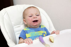 Crying baby in highchair Stock Image