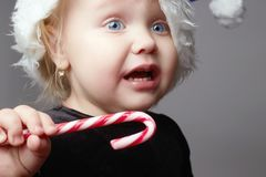 Crying baby. kid with candy. sad child in christmas time. Crying baby. little santa girl. kid with lollipop candy. sad child in christmas time with a gift Royalty Free Stock Photography
