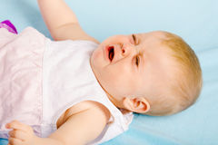 Crying baby lying on plaid Royalty Free Stock Image
