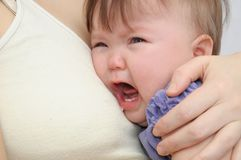 Crying baby at the mother on hands. Soothing upset child embracing and calming Stock Photos