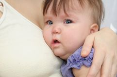 Crying baby at the mother on hands. Soothing upset child embracing and calming Stock Photo
