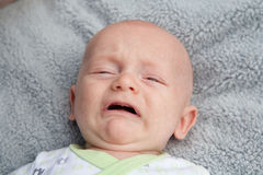 Crying Baby With Mouth Open. A baby crying with a gray blanket in the background Stock Photography
