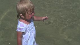 Crying baby with open arms standing in water. Disobedient child. Naughty crying little girl. Children`s crying. Terrified child stock video