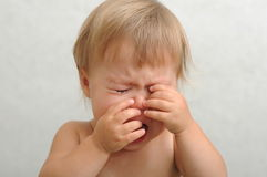 Crying baby rubbing her eyes Royalty Free Stock Image