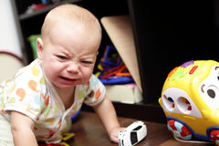 Crying baby. Sitting on a floor at home Royalty Free Stock Photo