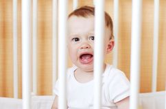 Crying baby in white bed Stock Photos