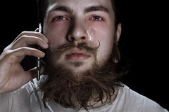 Crying Bearded Man. Holding A Smartphone Near Your Ear Royalty Free Stock Images