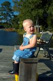 Crying big Tears. Young boy sits on a wooden bench on dock.  He has a huge tear runing down his face.  He has on denim overalls and black rubber boots Royalty Free Stock Image
