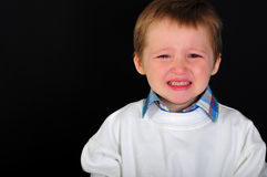 Crying blond boy on a black background Stock Images