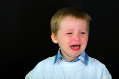 Crying blond boy  on a black background Royalty Free Stock Image