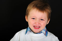 Crying blond boy with blue eyes on a black background Royalty Free Stock Photos