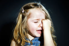 Crying blond little girl with focus on her tears. Crying cute little girl with focus on her tears on dark background Royalty Free Stock Images