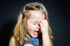 Crying blond little girl with focus on her tears. Crying cute little girl with focus on her tears on dark background Royalty Free Stock Image