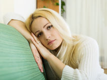Crying blonde woman. On sofa Royalty Free Stock Photography