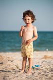 Crying boy on the beach. A small child is standing by the sea and crying. The kid is standing on the sandy beach royalty free stock image