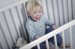 Crying boy in bed Royalty Free Stock Photo