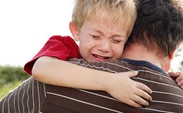 Crying Boy being comforted by his father. A crying young boy is comforted by his father Royalty Free Stock Image