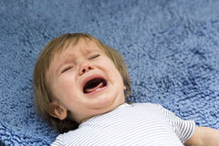 Crying Boy. A crying little boy lying on a blue carpet Royalty Free Stock Images