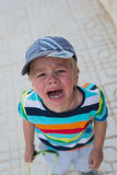 Crying boy standing on the street Stock Photo
