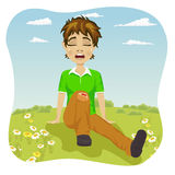 Crying boy with wounded leg in park. Crying boy with wounded leg in the park Royalty Free Stock Photography