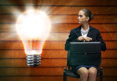 Crying businesswoman. Upset businesswoman sitting on chair with suitcase in hands Royalty Free Stock Image