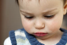 Crying child. Close up portrait of a sad crying small child; boy or girl Stock Photo