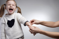 Crying child. Parent applying band aid to crying child Royalty Free Stock Photos