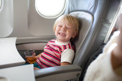 Crying child in airplane. Crying child with juice in airplane Stock Image