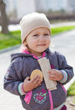 Crying baby eating. Crying child eating cookies in the street royalty free stock photo